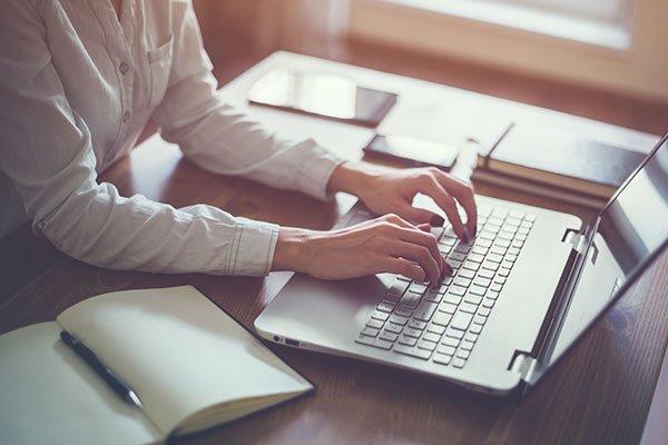 una donna che sta scrivendo su un computer portatile e accanto un libro aperto con una penna che funge da segnalibro