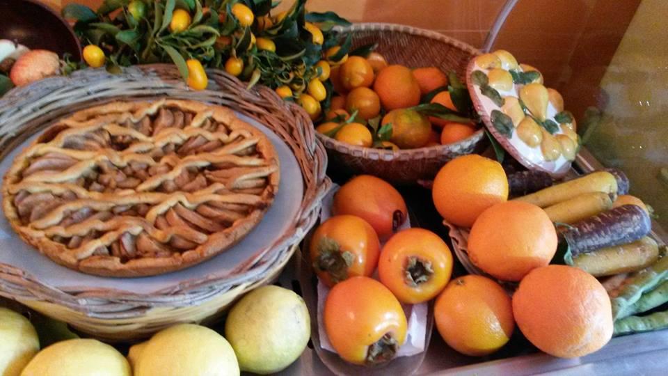 una crostata e accanto dei cachi e dei mandarini