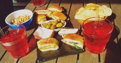 due cocktail rossi e degli stuzzichini da aperitivo