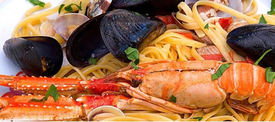 un piatto di spaghetti con scampi, vongole e cozze