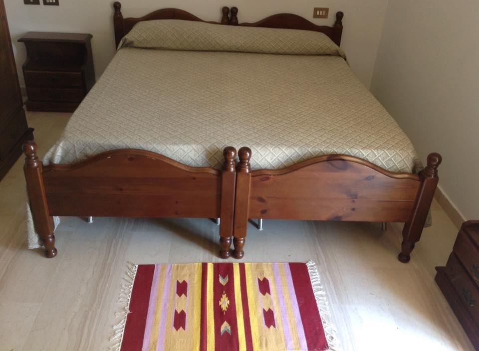 una camera con un letto e un comodino in legno