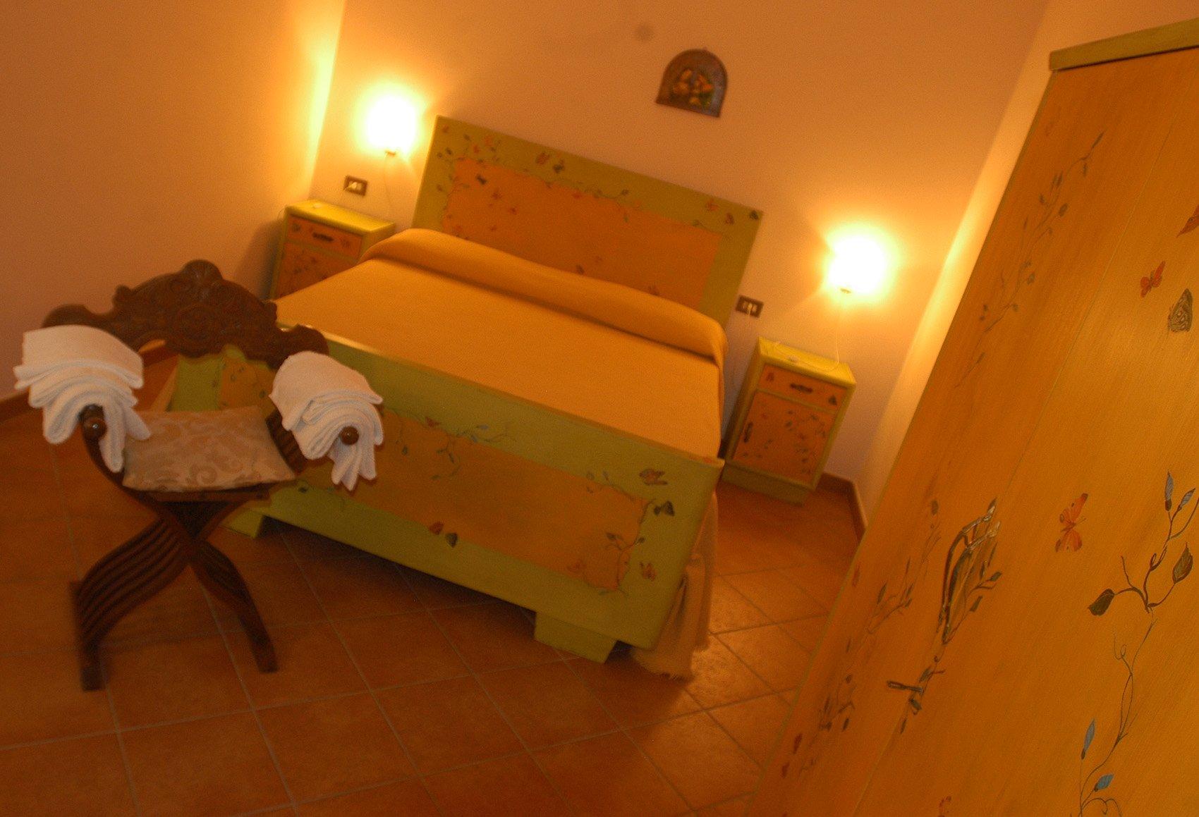 una camera con un letto, un armadio e comodini gialli