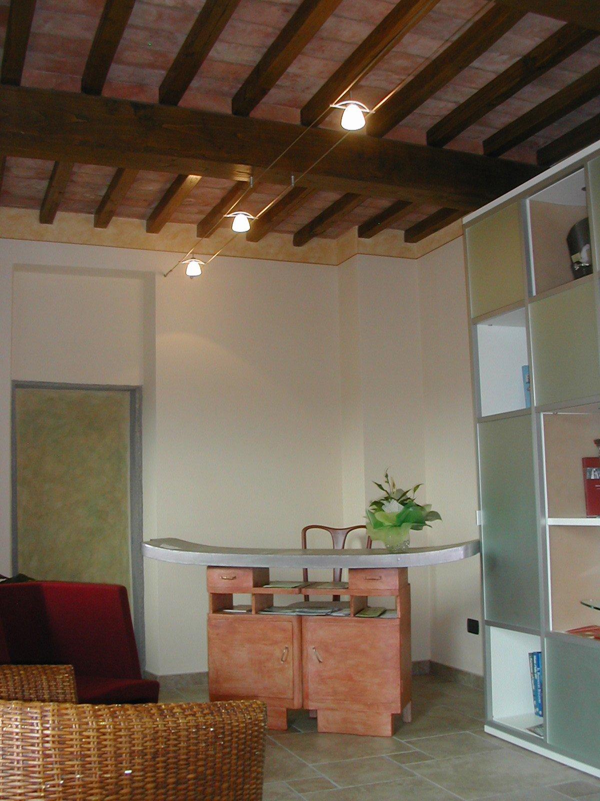 un tavolo con un vaso con sopra una pianta, un armadio bianco con ante colorate, una poltrona rossa e una di paglia