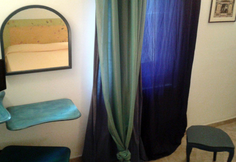 Un armadio con delle piccole ante colorate,una poltrona di paglia e un tavolo con sopra un vaso con una pianta