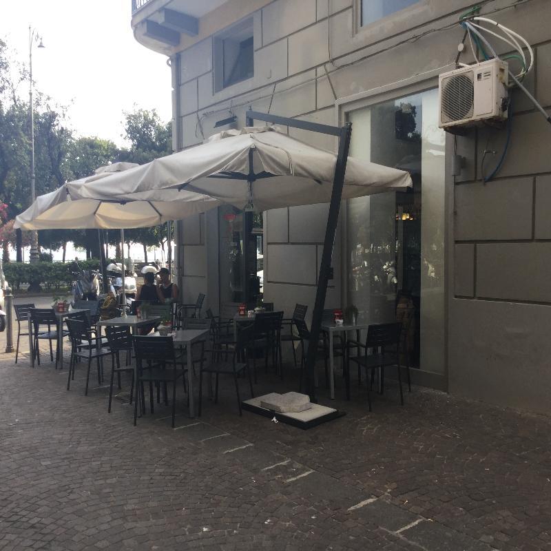 tavoli e sedie all'aperto sotto un ombrellone