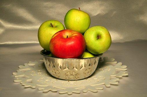 un cesto con tre mele verdi ed una rossa
