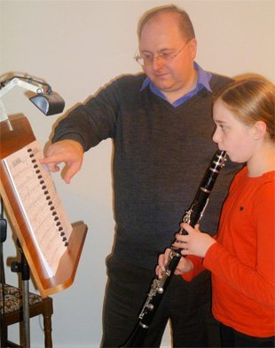 Mark teaching a young lady to play the clarinet