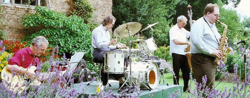 Photo of our jazz quartet playing music in a garden