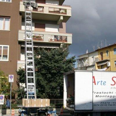 una scala estensibile vicino a un condominio e accanto un camion dei traslochi bianco