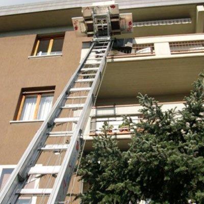 vista dal basso verso l'alto di una scala estensibili per traslochi vicino a un condominio