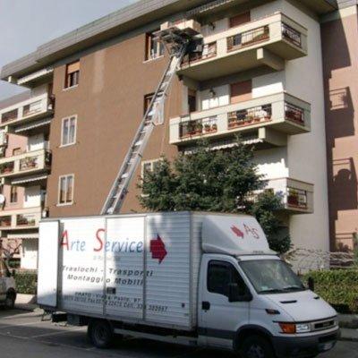 un camion bianco parcheggiato vicino a un condominio marrone e una scala estensibile