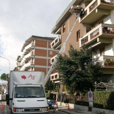 un camion bianco e dietro un condominio