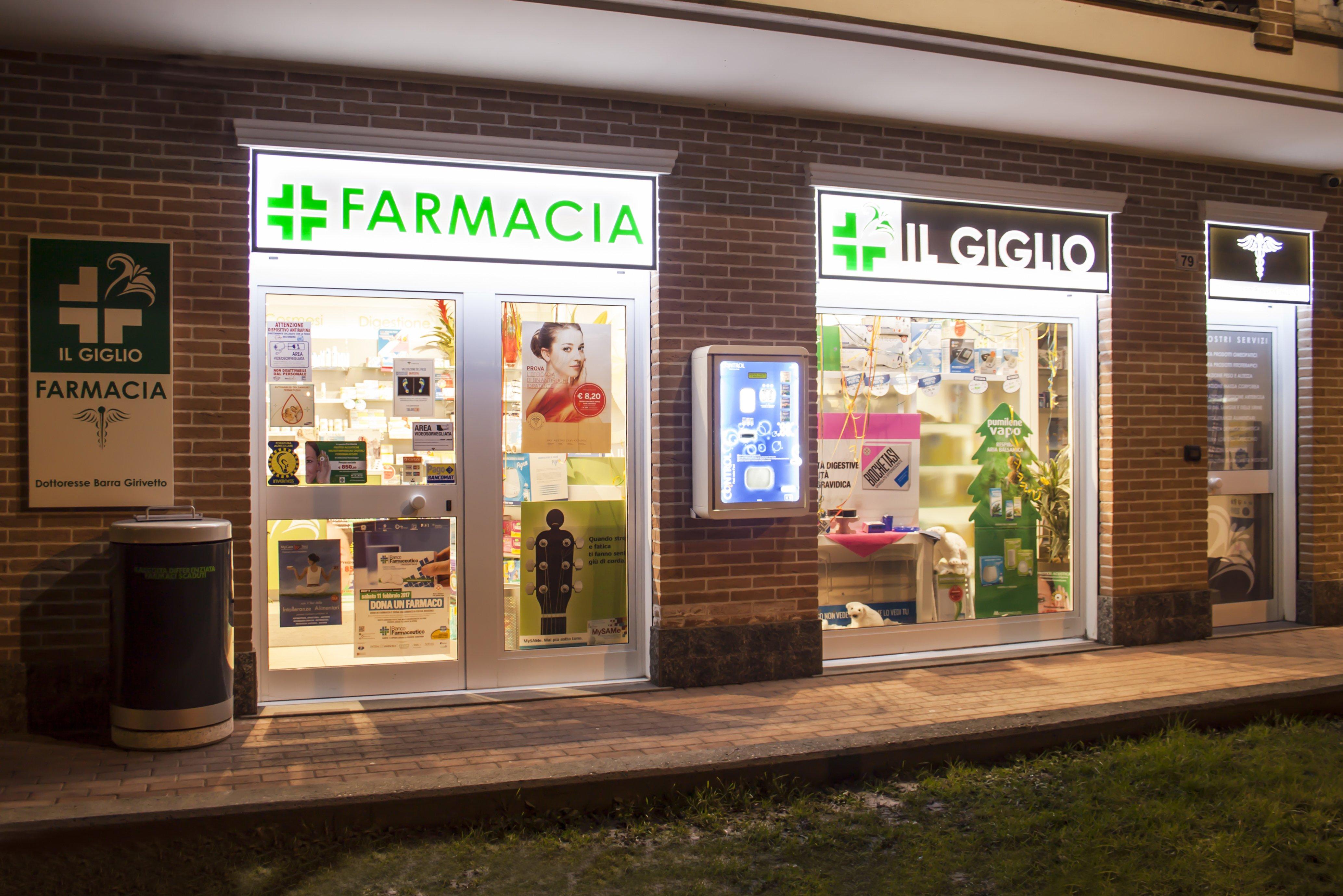 Entrata della farmacia vista dall'esterno con due vetrine e macchinetta ventiquattro ore per sistemi contraccettivi a Caselle Torinese, TO
