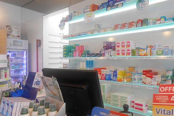 vista del bancone con un monitor e sugli scaffali esposizione di medicinali