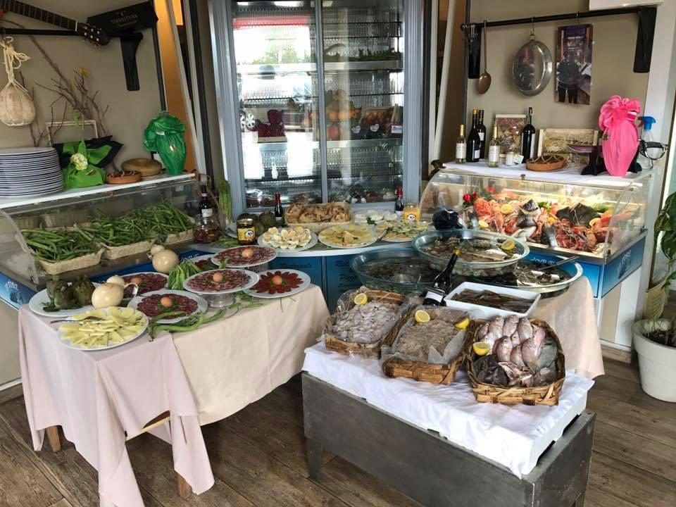 Tavole con piatti di salumi, formaggi,pesci e verdure