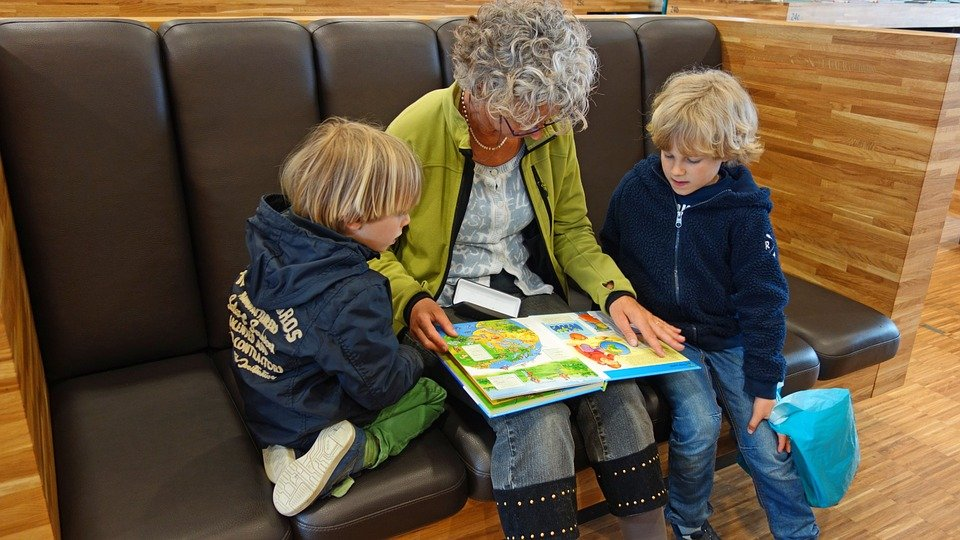 Older babysitter reading to twins