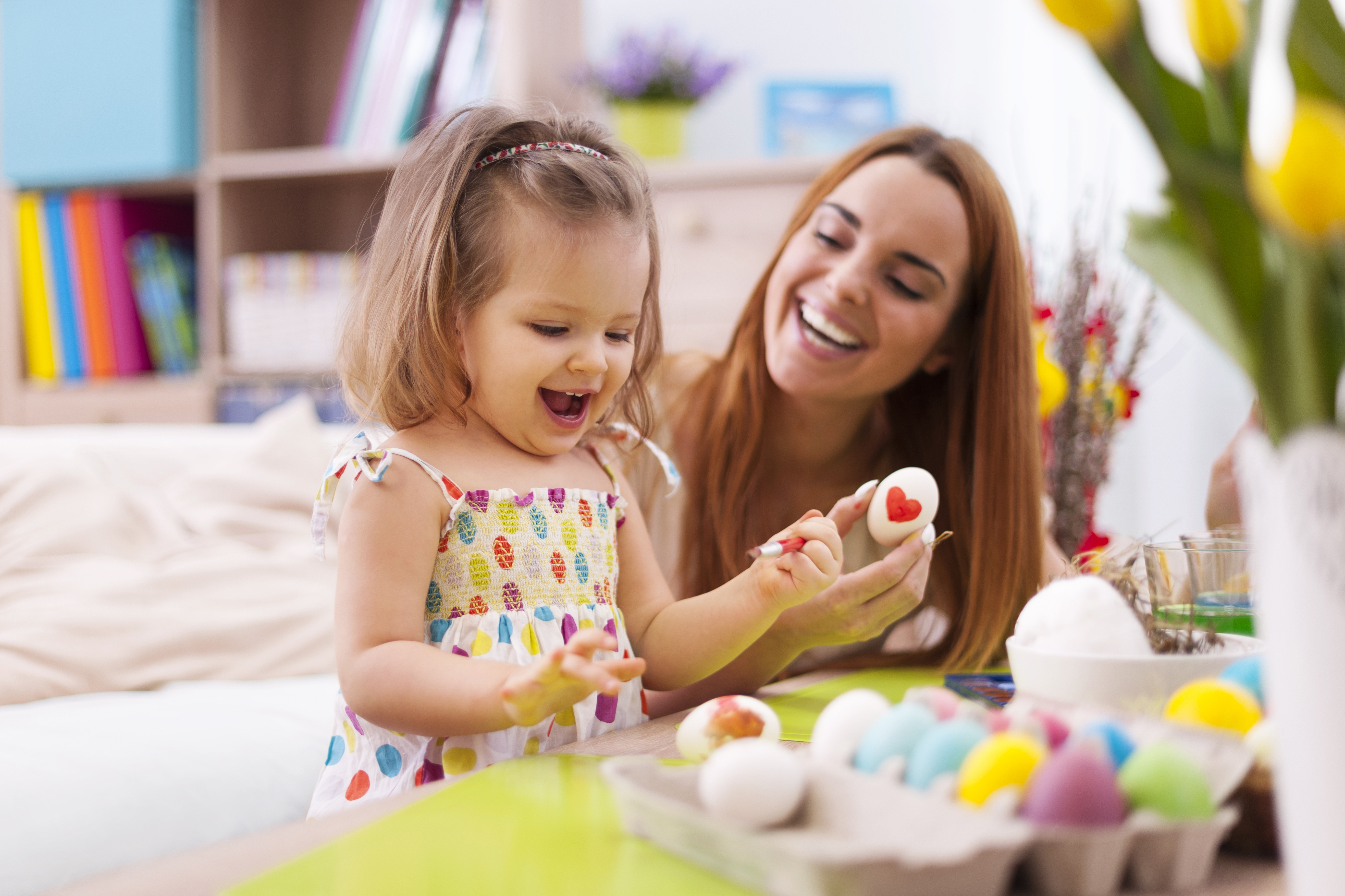 Babysitter painting eggs with toddler girl