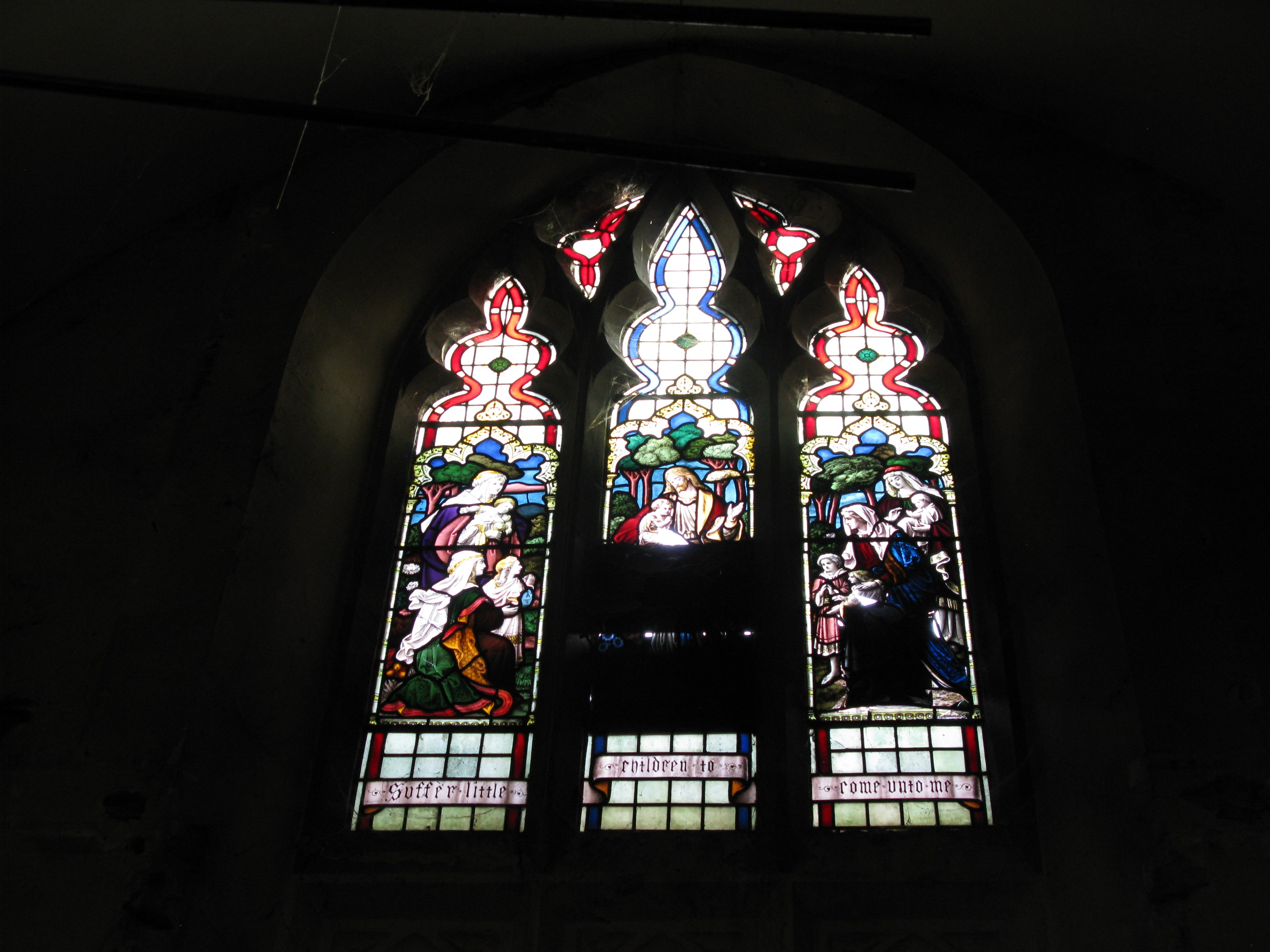 partially boarded stained glass window depicting saints