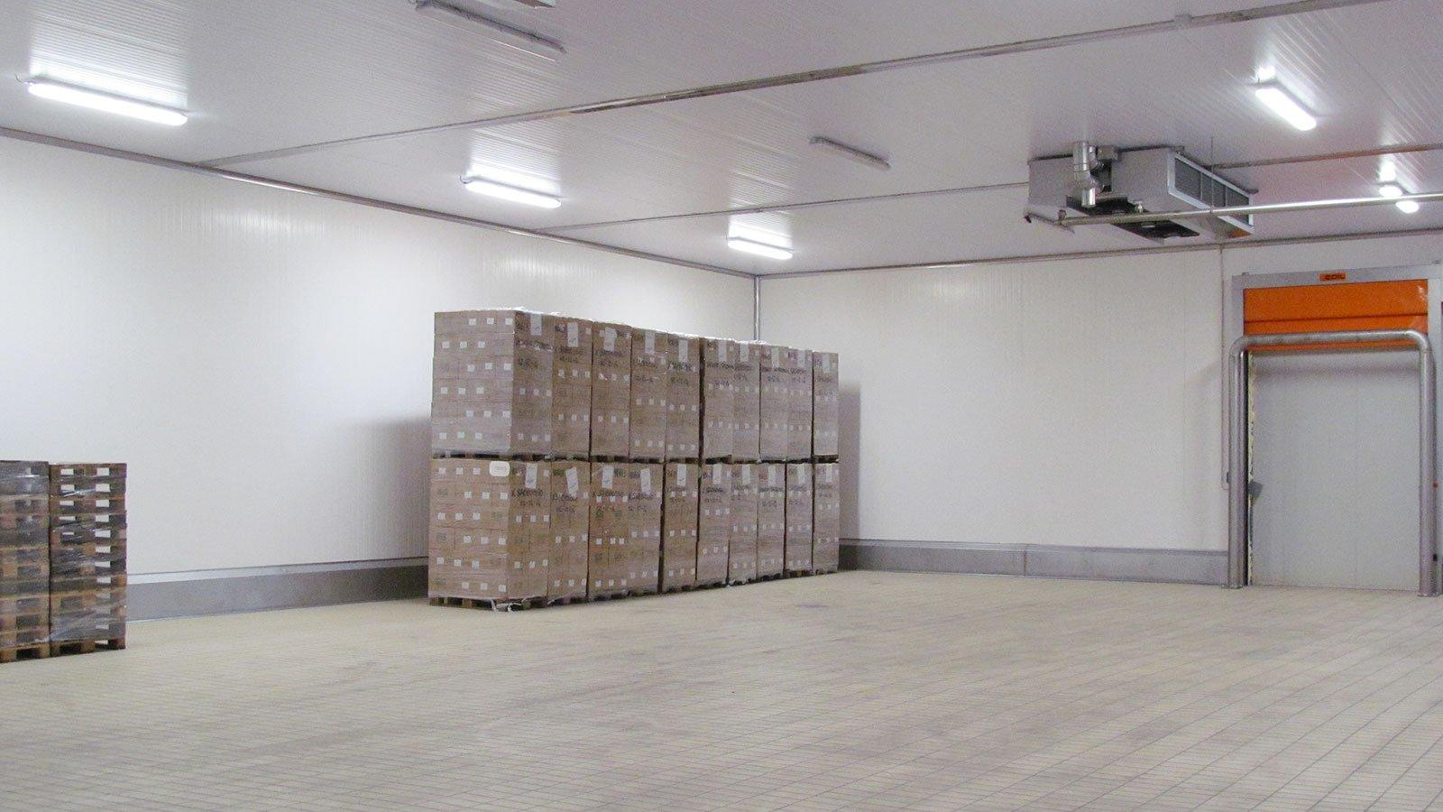 interno di un magazzino con sulla sinistra degli scatoloni su dei bancali e sulla destra una porta