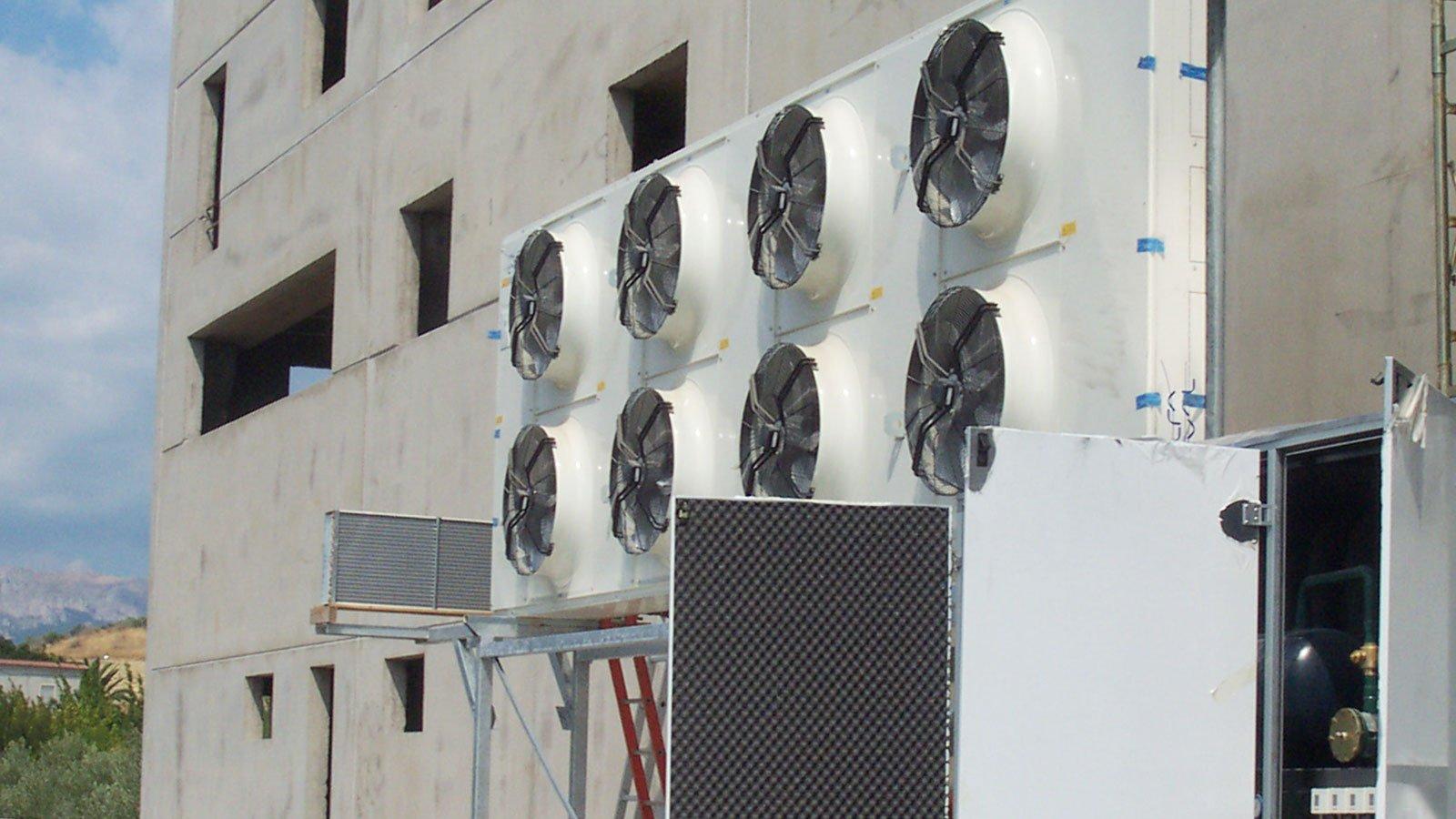 una serie di motori con delle eliche all'esterno di uno stabile in costruzione