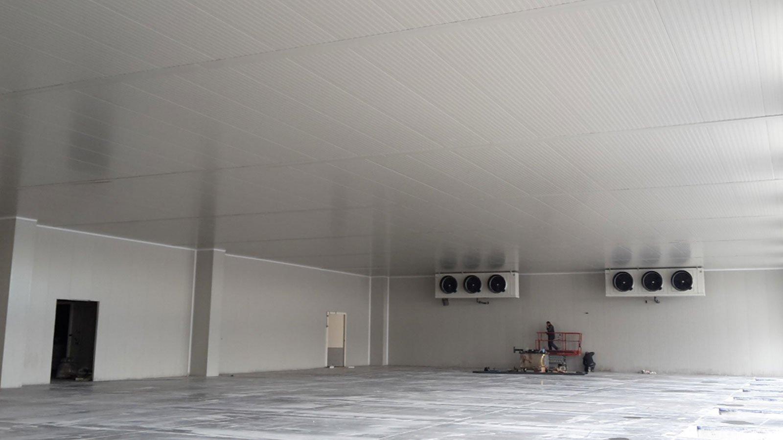 vista di un'ampia stanza vuota all'interno di uno stabile industriale con in fondo dei motori a muro