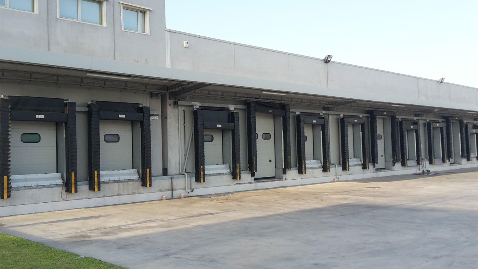 uno stabile industriale visto da fuori con una serie di porte con delle serrande in telo nero automatizzate