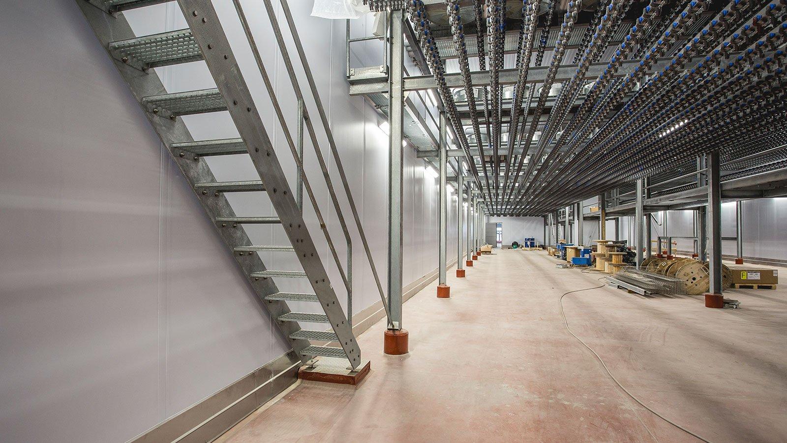 interno di uno stabile industriale con sulla sinistra una scala in ferro e in fondo del materiale da lavoro
