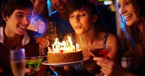 Girl blowing on candles on birthday cake surrounded by friends at party