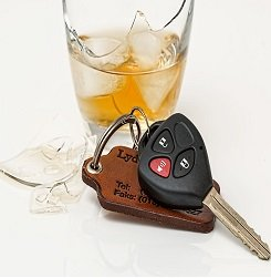 GBroken glass containing whiskey and car keys next to it.