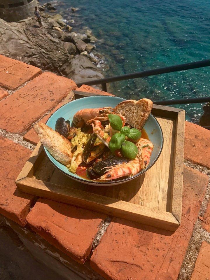 piatto di pesce su muretto con vista mare