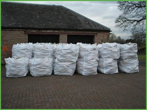 bags of timber stacked up against a shed