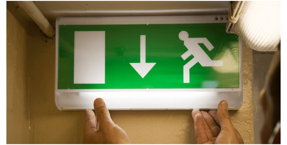 A fire safety sign and emergency lighting being installed on a wall, by City Fire Protection, Gloucester