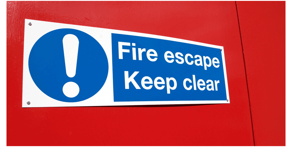A fire exit sign on a door, part of a range of fire safety signs sold by City Fire Protection, Gloucester