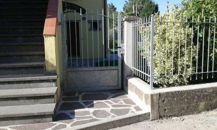 un cancello, sulla destra una ringhiera e sulla sinistra delle scale