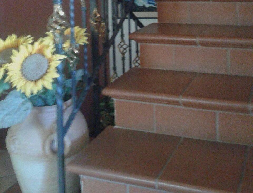 dei gradini di color arancione e accanto un vaso con dei girasoli