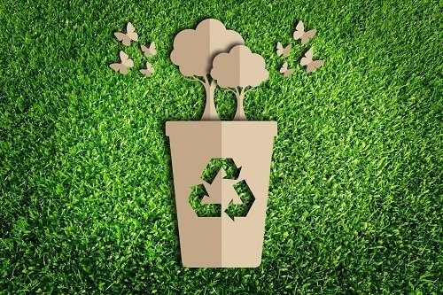 disegno di contenitore col simbolo del riciclo da cui sorgono alberi e farfalle sullo sfondo di un prato verde