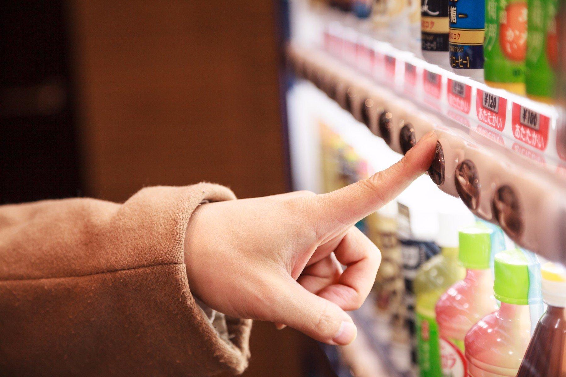 mano pigia il pulsante di un distributore automatico