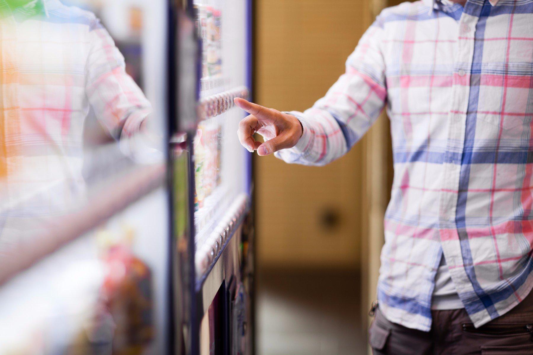 ragazzo seleziona prodotto sul distributore automatico