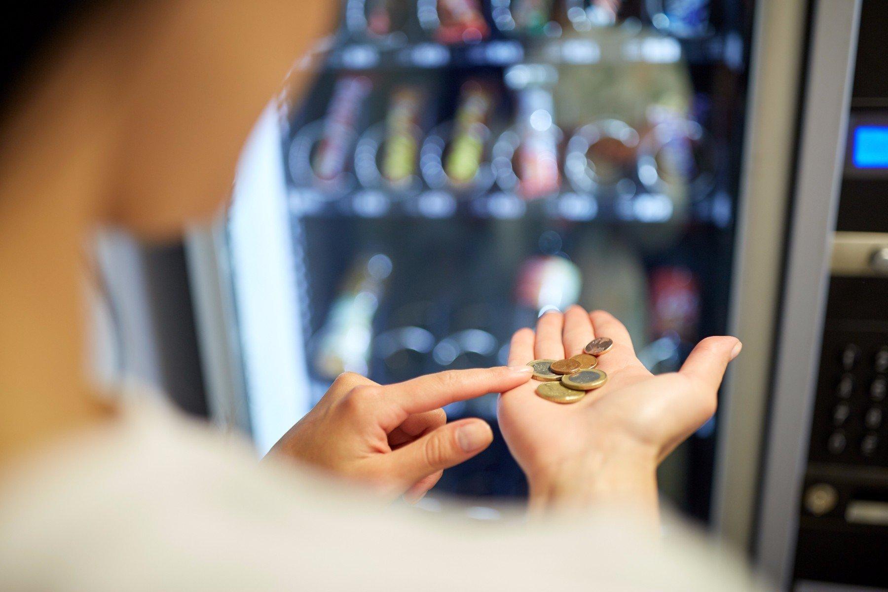 donna conta monetine di fronte a un distributore automatico