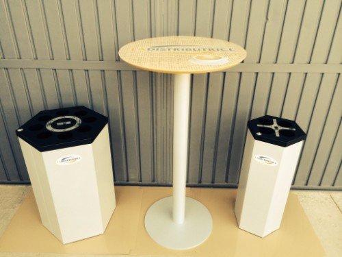 tavolino rotondo alto e bianco con accanto un cestino e una colonnina spegni sigaretta