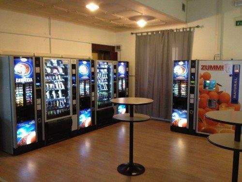 Angolo ristoro con tavolini e distributori automatici di caffè, snack e succhi