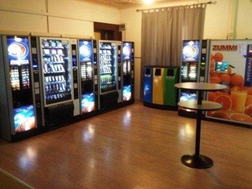 area ristoro con distributori automatici, tavolini e secchielli per la differenziata
