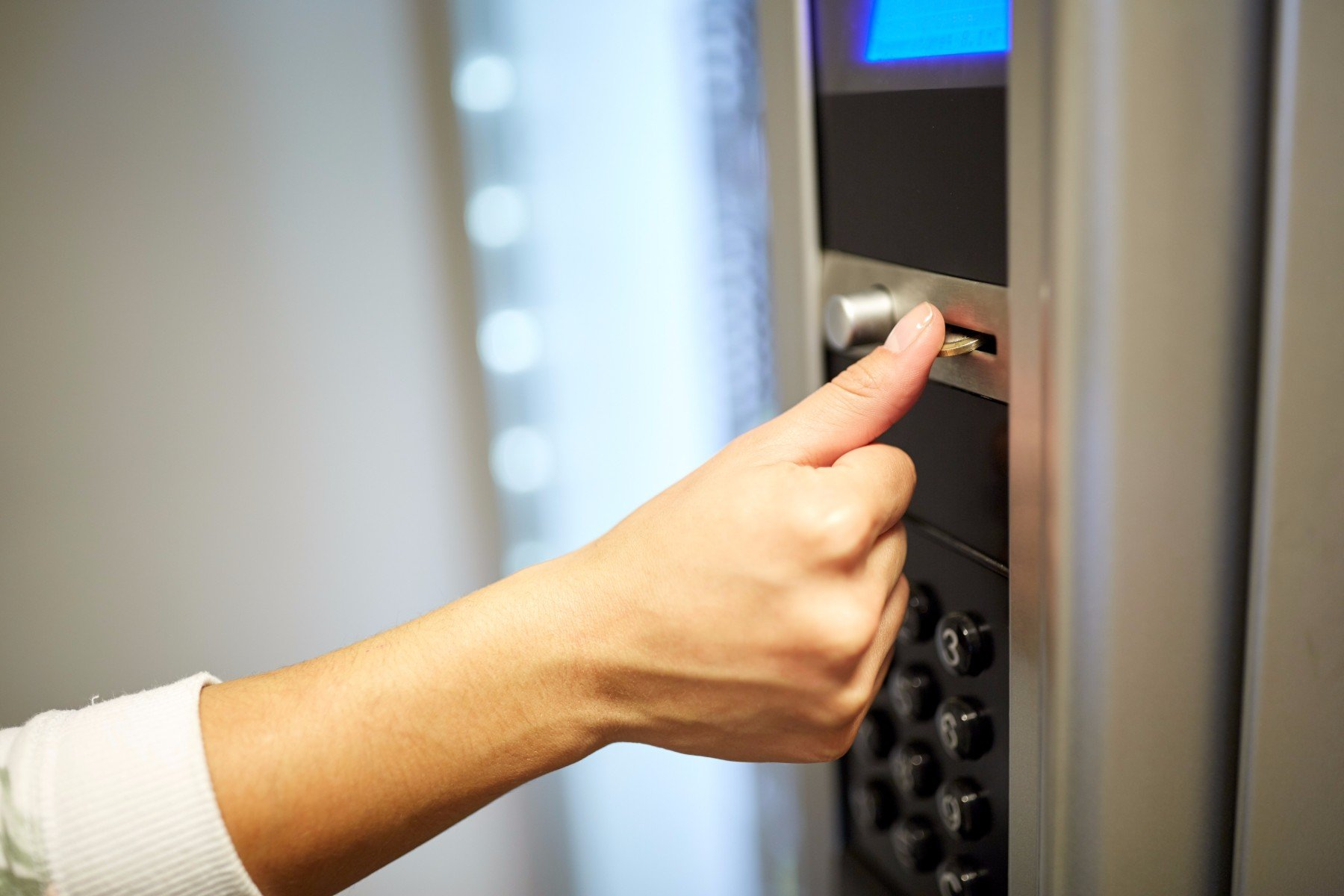 donna inserisce moneta nel distributore automatico