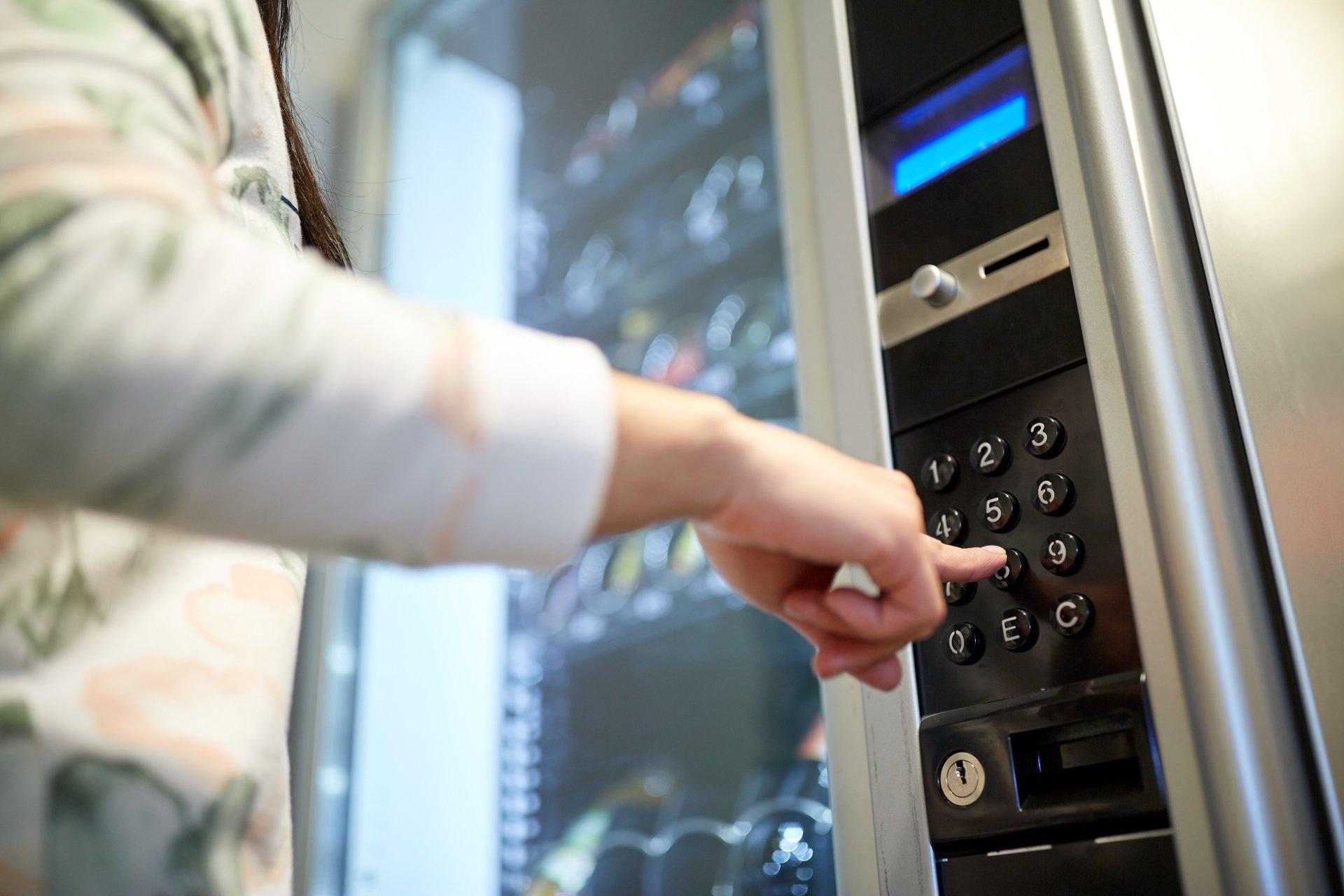 mano che digita il numero su un distributore automatico