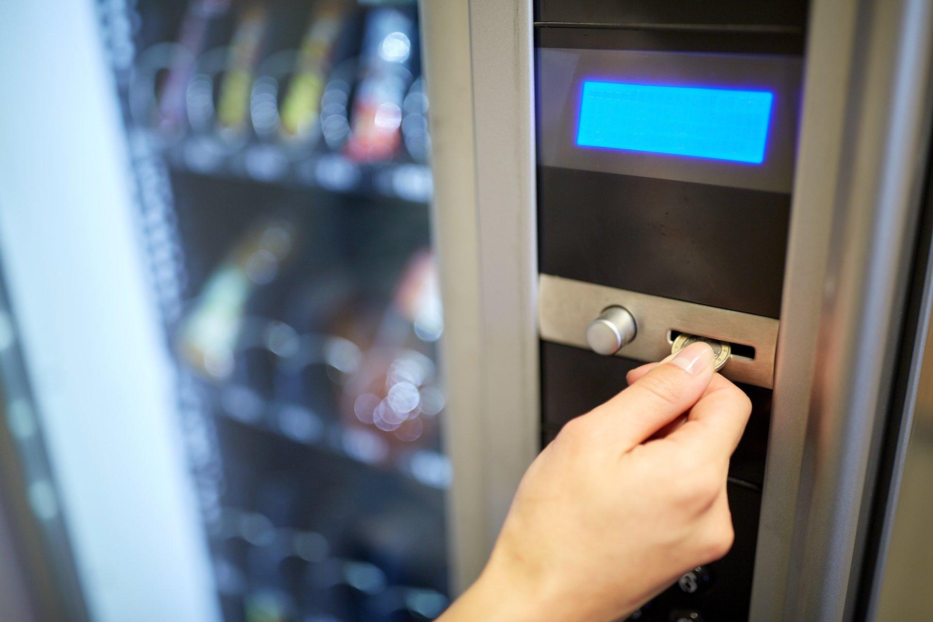 ragazza inserisce moneta in un distributore automatico