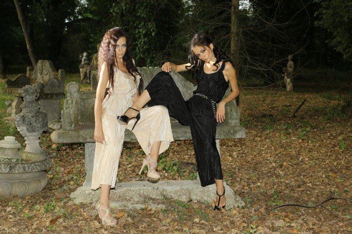 Due modelli con abiti a pantalone in chiffon su una panchina