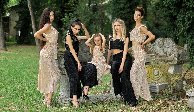 Due modelle in abiti neri e due e una bambina in abiti écrue
