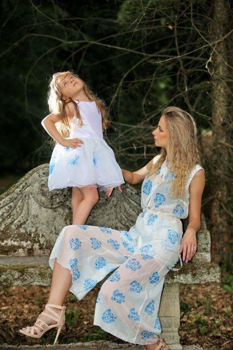 Una modella e una bambina bionde con abito bianco a fantasia floreale