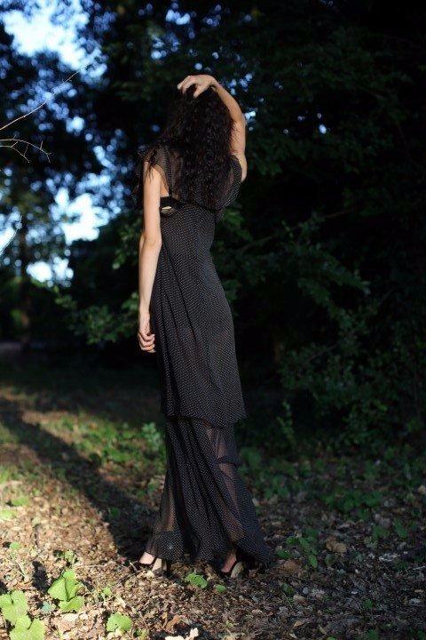 Modella con vestito nero trasparente a pois