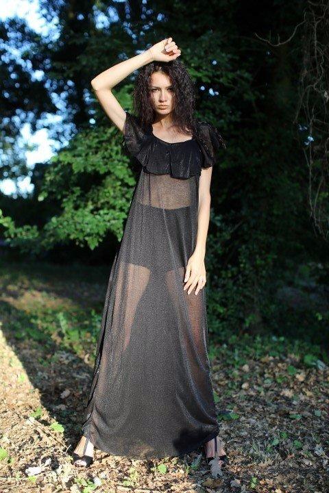 Modella con vestito nero trasparente con scollo a barchetta